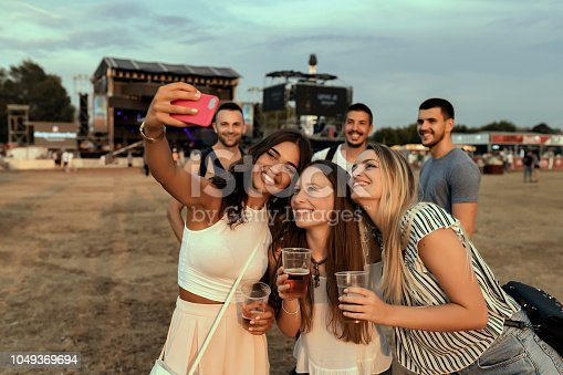 Girlfriends Making Selfie at the Summer Festival and having Fun Outdoors