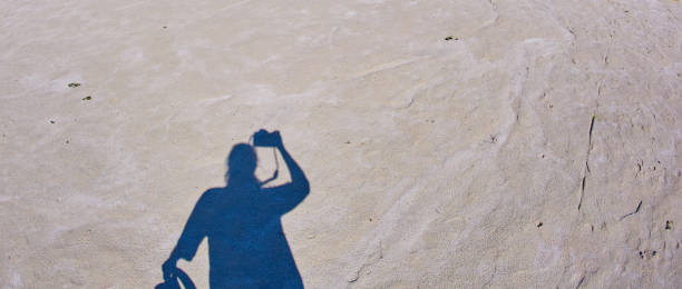 A self-portrait of a photographer with a camera in his hands casts a shadow on the sandy ground with a silhouette stock photo