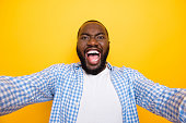 istock Self-portrait of attractive handsome wild manly mulato guy in casual checkered shirt, opened mouth, isolated over bright vivid yellow background 1055425280