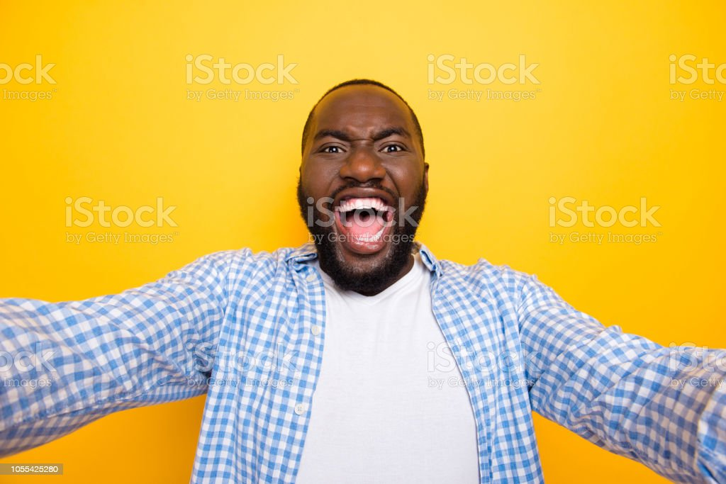 Self-portrait of attractive handsome wild manly mulato guy in casual checkered shirt, opened mouth, isolated over bright vivid yellow background stock photo