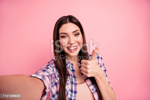 Self-portrait of her she nice-looking attractive cute charming shine winsome lovely cheerful straight-haired lady wearing checked shirt showing thumbup ad advert isolated on pink background.