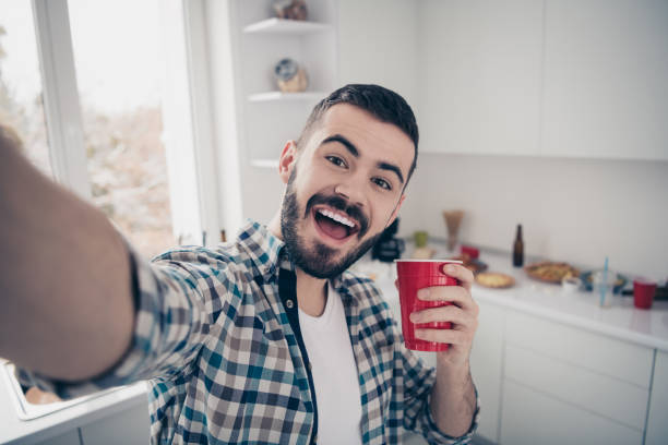 self-portrait of his he nice attractive cheerful cheery funny glad bearded guy wearing checked shirt having fun time vacation in modern light white interior style kitchen indoors - selfie foto e immagini stock