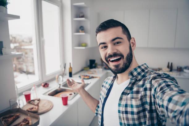 Autorretrato de su agradable atractivo alegre alegre alegre alegre chico barbudo alegre usando camisa a cuadros divirtiéndose invitando a visitar la cocina moderna de estilo interior blanco claro en el interior - foto de stock
