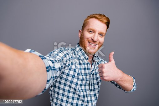 1092211952 istock photo Self-portrait of nice positive cheerful funny handsome attractive trendy man wearing checkered shirt showing thumbs-up sign isolated over grey pastel background 1092247752
