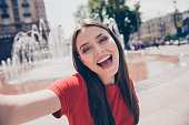 Self-portrait of straight-haired young beautiful smiling foolish girl wearing casual red t-shirt outside, traveling abroad, excited, opened mouth