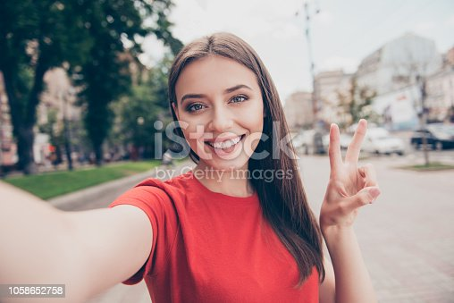 Self-portrait of straight-haired young beautiful smiling girl wearing casual red t-shirt outside, traveling abroad, showing v-sign