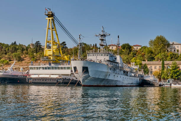 self-propelled floating crane spk-54150 and demagnetization vessel sr-137 at the pier of the south bay of sevastopol. black sea fleet of russia. - degauss stock pictures, royalty-free photos & images