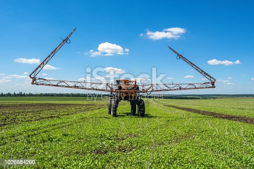 self-propelled sprayer works on a field under a blue sky with clouds.