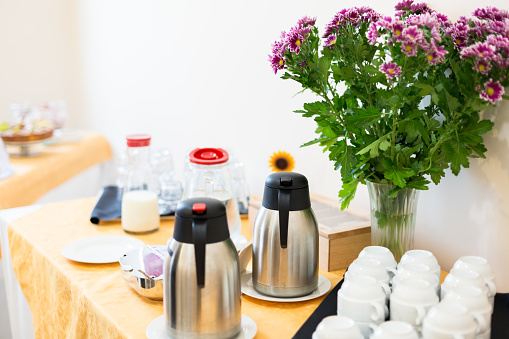 Self-service breakfast and decorative vase with purple flowers. Kettles, coffee cups and milk glass bottle