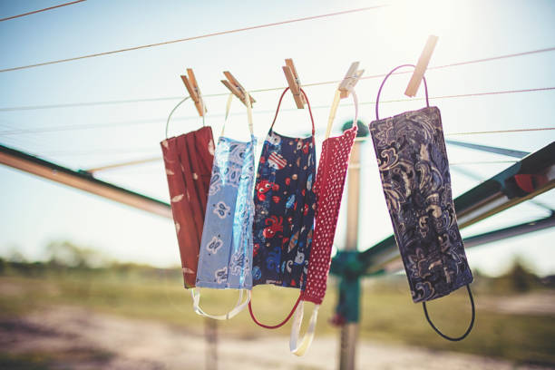 Self-sewn mouth-nose masks against corona viruses hang on the clothesline to dry. stock photo