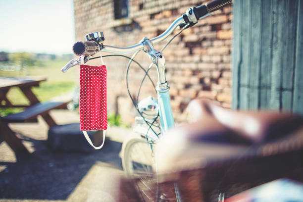 Self-sewn nose-mouth mask for protection against viruses and bacteria hangs on the bicycle handlebar in the sun stock photo