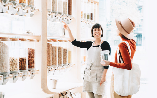 istock Seller advising woman in her purchase of groceries without plastic packaging in zero waste shop. 1190360821