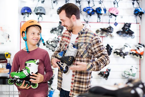 istock Seller assisting boy in choosing roller-skates 1044132084