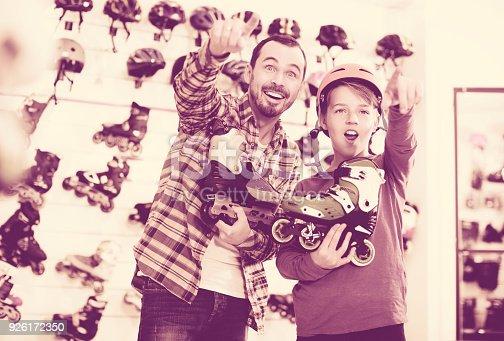 istock Seller assisting boy in choosing roller-skates 926172350