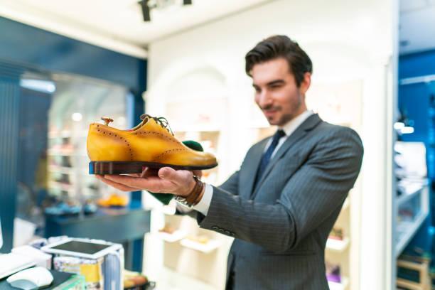Seller clerk holding elegant shoes in store stock photo