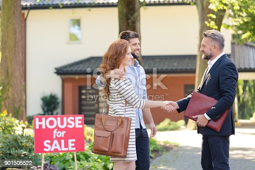 istock Seller congratulating couple buying house 901505522