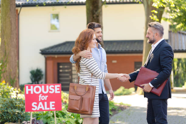 Seller congratulating couple buying house stock photo