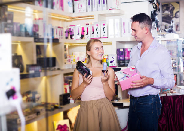 Seller consulting customer with assortment Positive seller consulting customer with assortment of adult products in store sex toy stock pictures, royalty-free photos & images