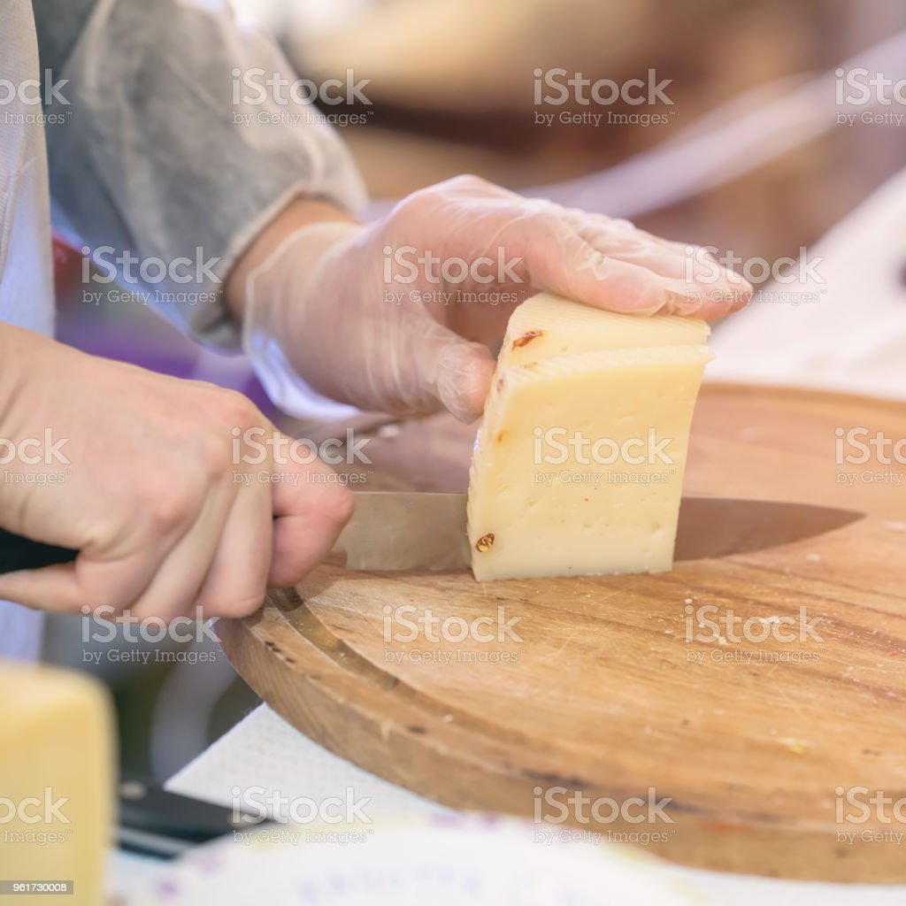 Seller cuts and sells cheese, cut cheese heads on wooden market board. Hands with knife close-up. Selective focus. Gastronomic dairy produce, real scene, food market stock photo
