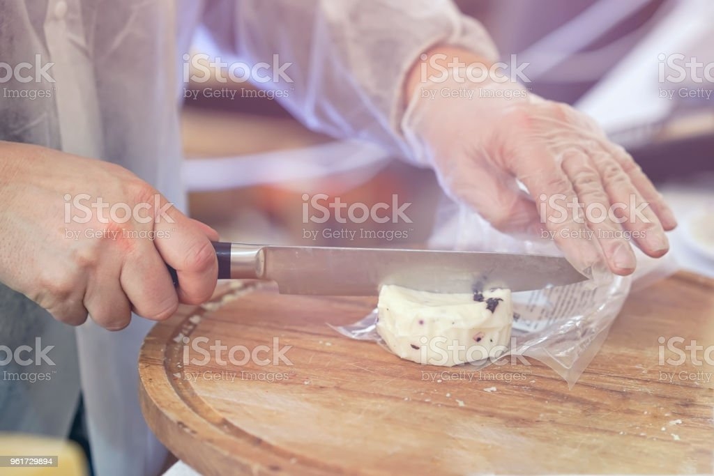 Seller cuts, sells cheese with truffle, cut cheese heads on wooden market board. Hands with knife close-up. Gastronomic dairy produce, real scene, food market stock photo