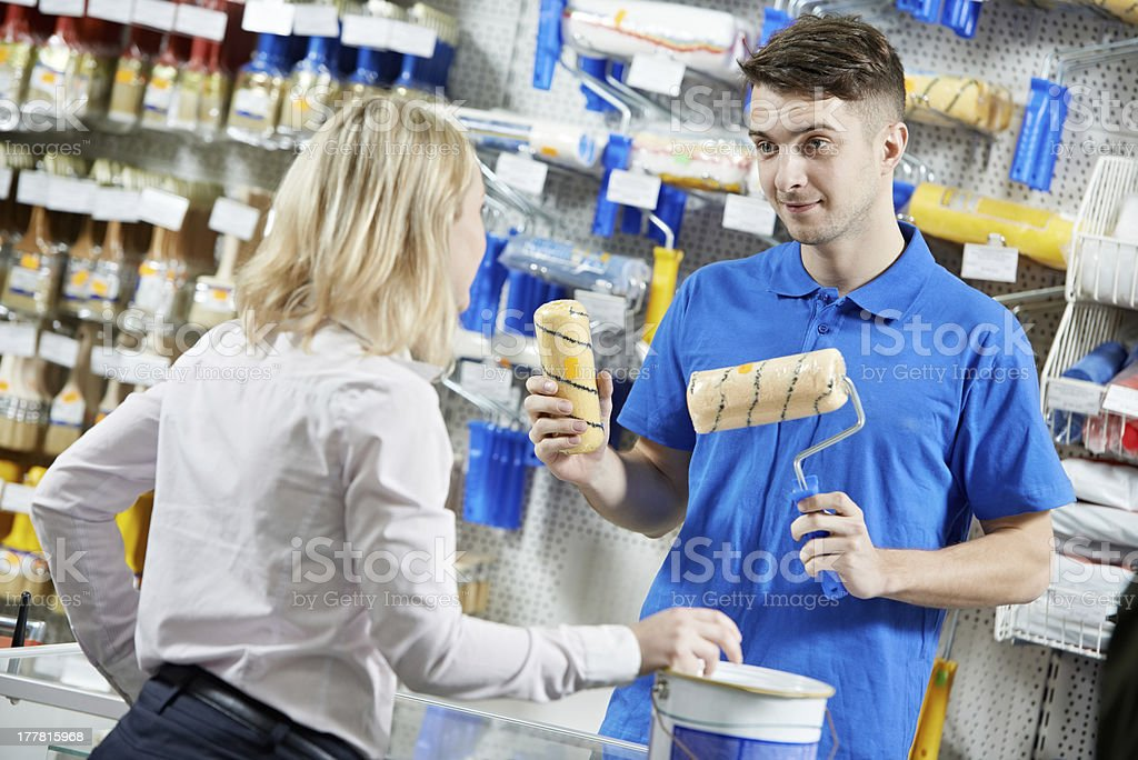 Seller demonstrating paint roller to buyer stock photo