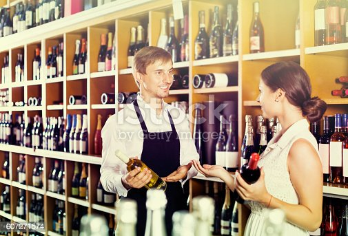 istock Seller helping woman customer with bottle of wine 607271574