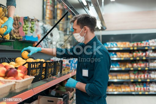 istock seller in a protective mask standing in front of the counter with fruit 1219973370