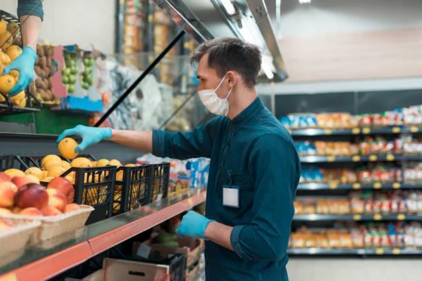 Verkäufer in einer Schutzmaske, die mit Früchten vor dem Tresen steht – Foto