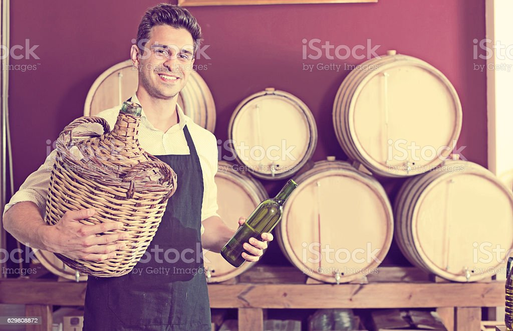 Seller in apron holding big wicker bottle with wine stock photo