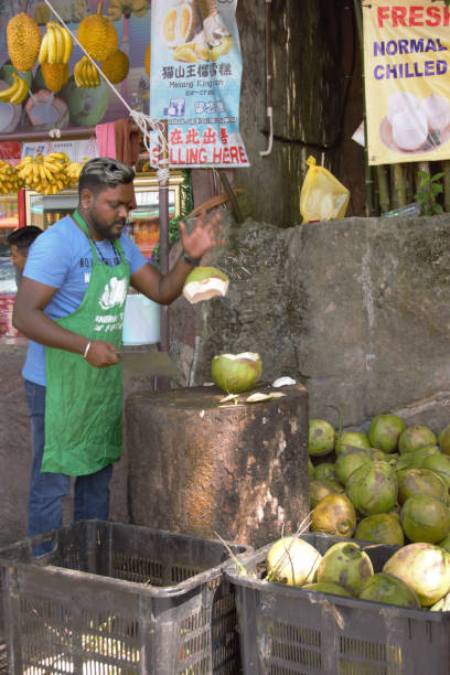Seller of coconuts Kuala Lumpur -north,Malaysia; 30-December 2019; In the direct surrouding of Batu Caves. A male seller of coconuts is chopping the nuts for refreshment, near the road on a small market. Lot of local details. batu caves stock pictures, royalty-free photos & images