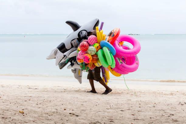 vendedor de juguetes inflables y natación vueltas va a lo largo de la playa en isla mauricio - vuelta completa fotografías e imágenes de stock