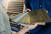 istock seller showing wooden texture laminate material samples to customer 1306105225
