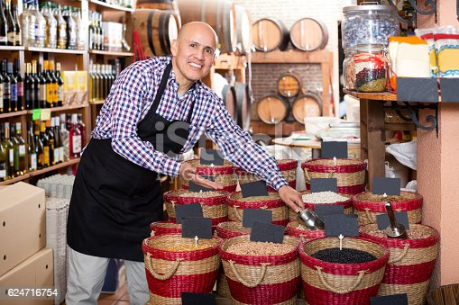 istock Seller taking dried beans with scoop from basket 624716754