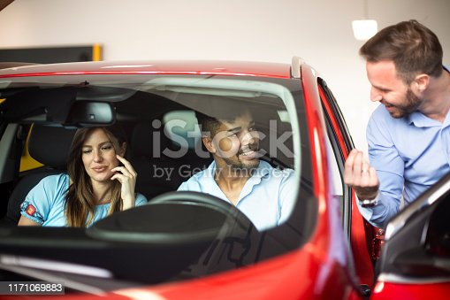 939005154 istock photo Seller using his skills in an auto salon with a young couple buying a new car 1171069883