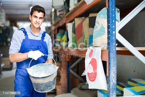 istock Sellerman is placing buckets for putty 1147266570