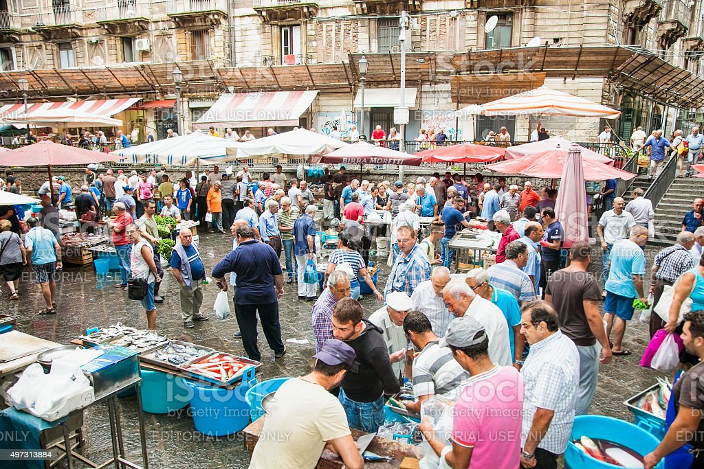 Sellers and byers on famous fish market in Catania, Italy. stock photo