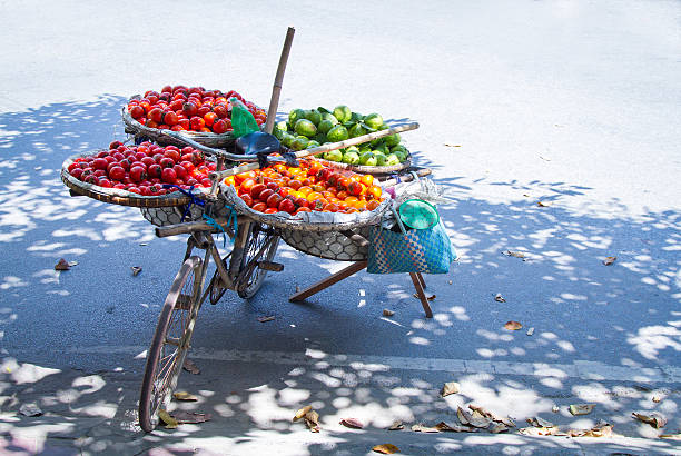 selling fruit A woman waiting for customers to come to sell the fruit in the basket of his car in Nam Dinh Viet Nam asian market stock pictures, royalty-free photos & images