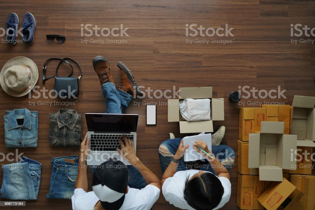 Selling online ideas concept, Man working laptop and women notebook with fashion clothes accessories and postal parcel for sale, Top view overhead on wood floor background Selling online ideas concept, Man working laptop and women notebook with fashion clothes accessories and postal parcel for sale, Top view overhead on wood floor background Adult Stock Photo