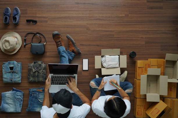 selling online ideas concept, man working laptop and women notebook with fashion clothes accessories and postal parcel for sale, top view overhead on wood floor background - ecommerce foto e immagini stock