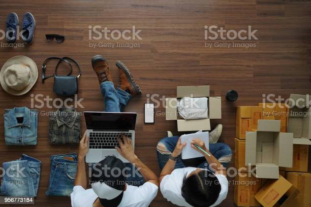 Selling Online Ideas Concept Man Working Laptop And Women Notebook With Fashion Clothes Accessories And Postal Parcel For Sale Top View Overhead On Wood Floor Background Stock Photo - Download Image Now