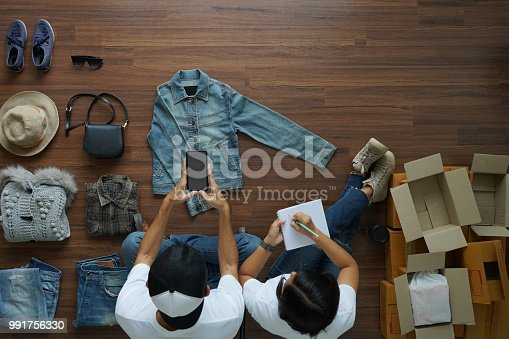 istock Selling online ideas concept small business owner, Top view Men and women  taking photo to shirts with cell telephone or smartphone digital camera on wooden floor with postal parcel box 991756330