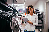 Beautiful woman using tablet while working in the store.