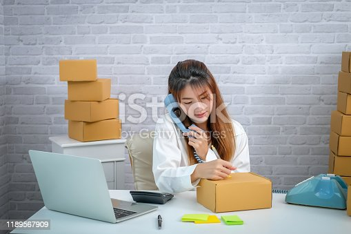 836871418 istock photo Selling products online. Portrait of a pretty woman phone talking to clients for shipping. Pack and delivery to the customer. 1189567909