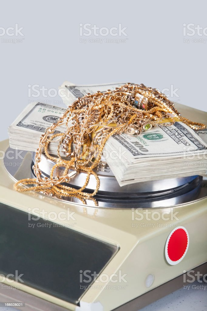 selling scrap gold on a penny weight scale stock photo