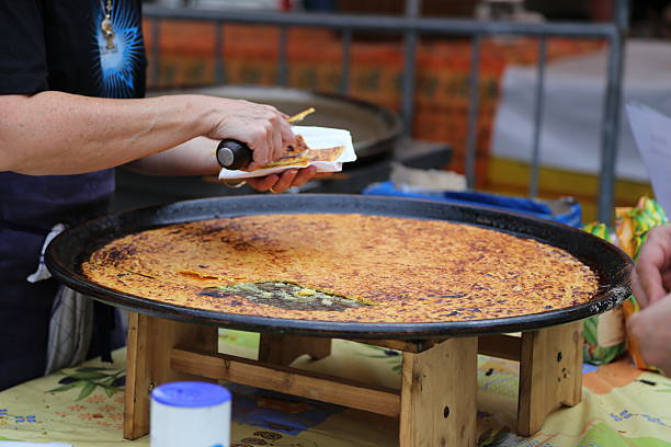 selling socca (farinata) Farinata, socca, or cecina is a sort of thin, unleavened pancake or crêpe of chickpea flour originating in Genoa and later a typical food of the Ligurian Sea coast, from Nice to Pisa. farinata stock pictures, royalty-free photos & images