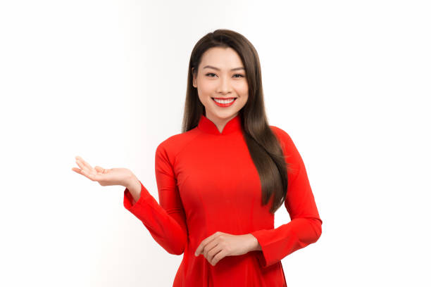 selling time, discounts for lunar new year, cute woman in ao dai showing copy space on her palm - ao dai stock photos and pictures