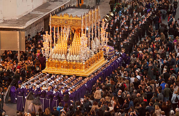 Semana Santa in Malaga: procession of Rescate brotherhood Malaga, Spain - March 22, 2016: eight rows of men dressed in purple robes, carry a heavy float with a statue of Virgin Mary, richly decoarted with golden ornaments and burning candles, in the Easter procession of the Rescate brotherhood on holy Tuesday. The procession is watched by many spectators .  religious celebration stock pictures, royalty-free photos & images