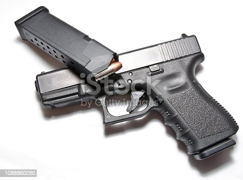 A semi automatic black pistol with a loaded pistol magazine laying on top of it on a white background