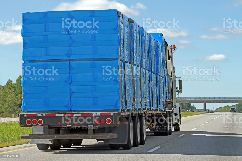 Semi Flatbed Truck Hauling A Covered Shipment Of Styrofoam stock photo
