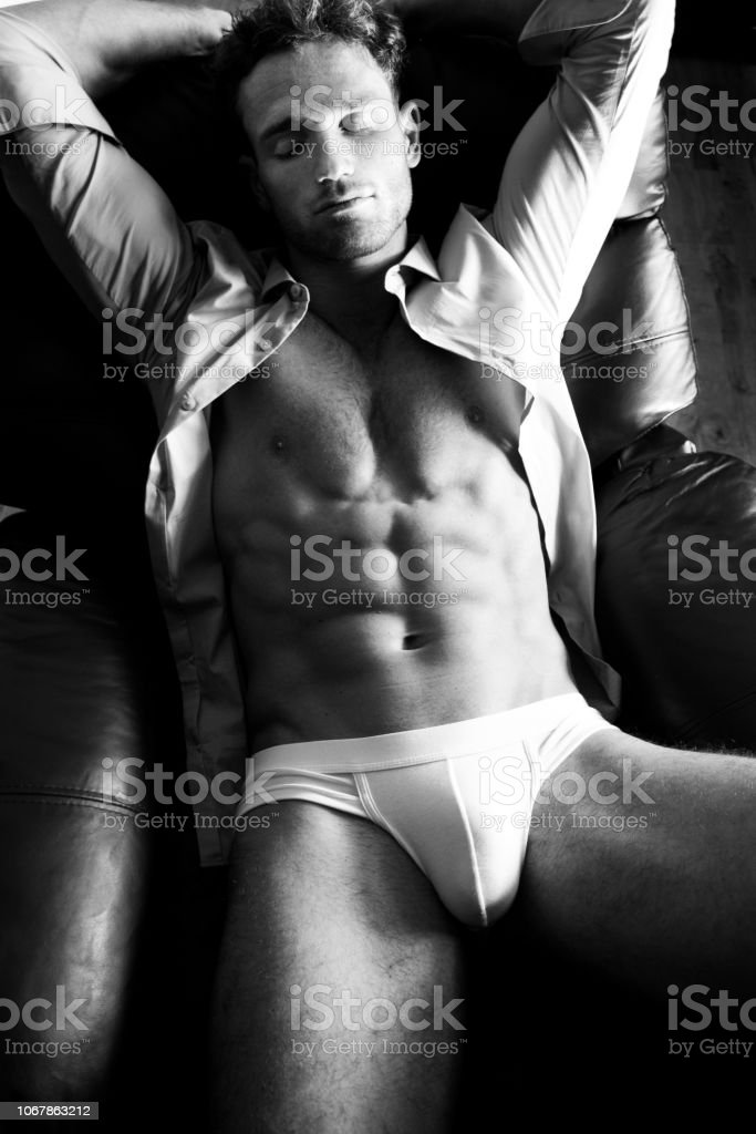 Semi naked handsome blonde man sleeping in leather armchair with open shirt revealing sixpack abs and wearing briefs stock photo